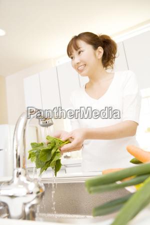 japanese woman washing a vegetable