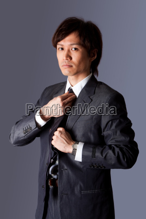 successful asian business man fixing tie