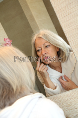 mujer mayor que aplica la crema