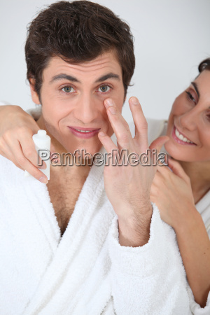 young couopke applying moisturizer on their