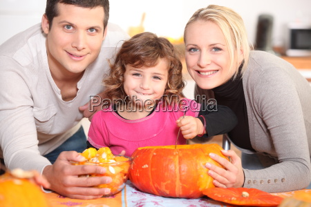 a family carving a pumpkin
