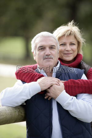 affectionate couple leaning against fence
