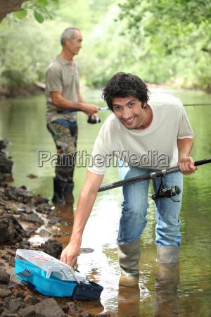 men fishing in a river