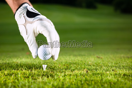 hand holding golf ball on the