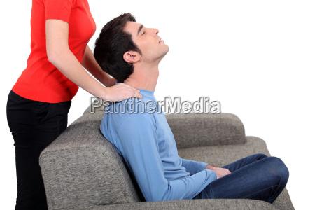 woman giving husband neck massage