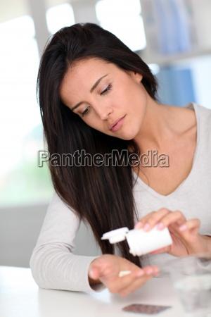 woman taking drugs to releave headache