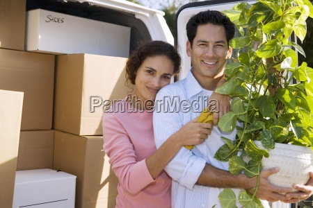 couple moving house standing beside van
