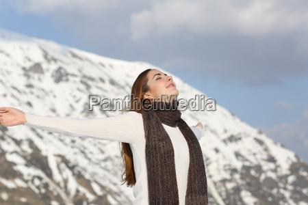woman breathing fresh air raising arms
