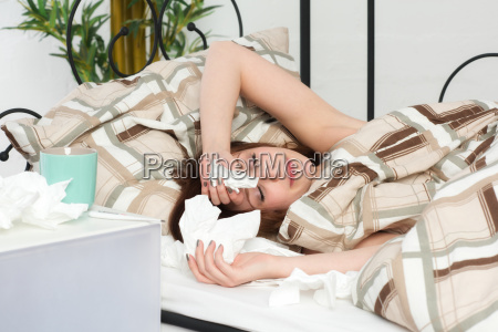 young sick woman lying in bed