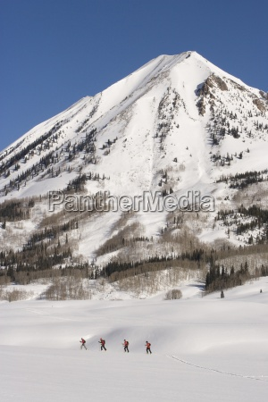 four skiers alpine tour in the