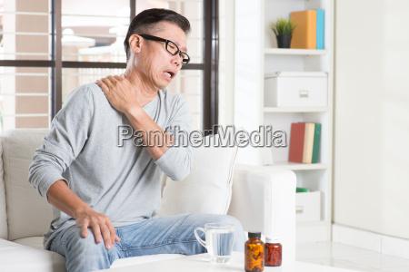 mature asian man shoulder pain