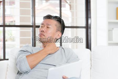 mature asian man shoulder pain while