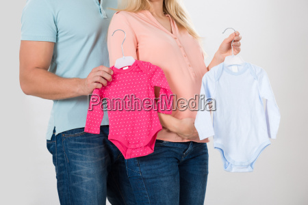 midsection of couple holding baby clothing