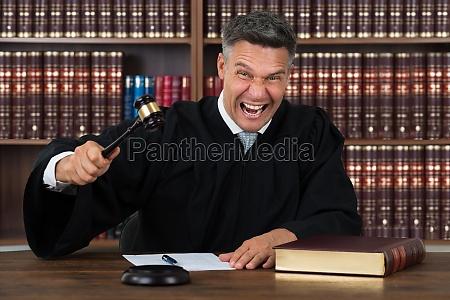 angry judge striking his gavel at