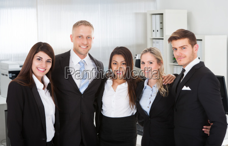business people standing arms around in