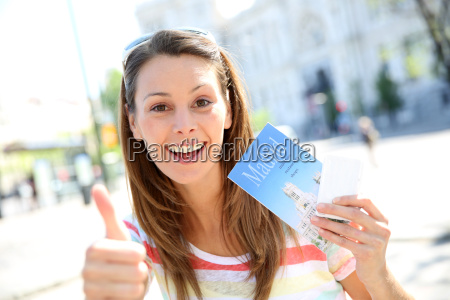cheerful girl in madrid holding city