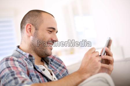 cheerful young man at home using