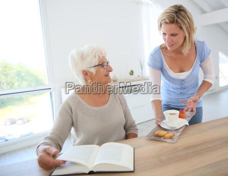 home helper giving tea to elderly