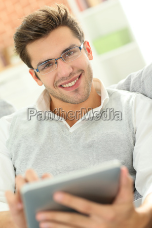 young man websurfing with tablet sitting