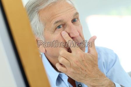 senior man applying anti aging lotion