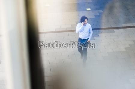 man walking on the street telephoning