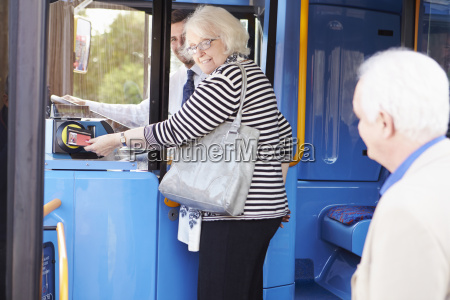 senior couple boarding bus and using