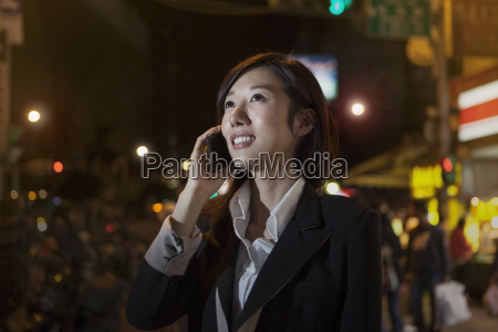 businesswoman on cellular phone night market