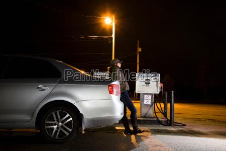 woman refueling car at night