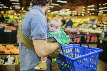 father holding baby son and shopping