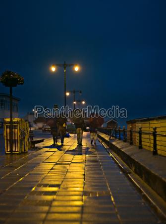 family walking on rainy city streets