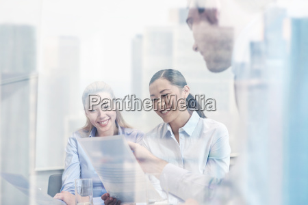 group of smiling businesspeople meeting in