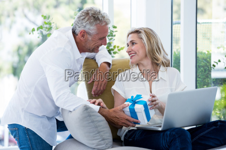 happy man giving gift to woman