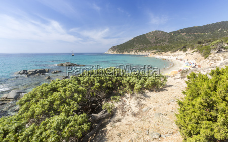 mediterranean vegetation frames the beach and
