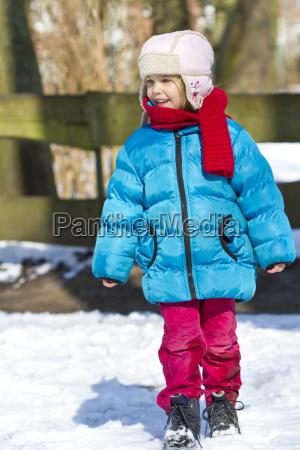 little girl wearing winter clothing watching