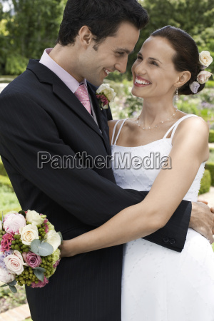 newlywed couple embracing in garden
