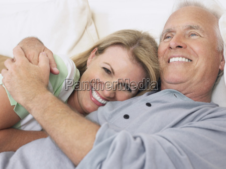 middle aged couple embracing in bed