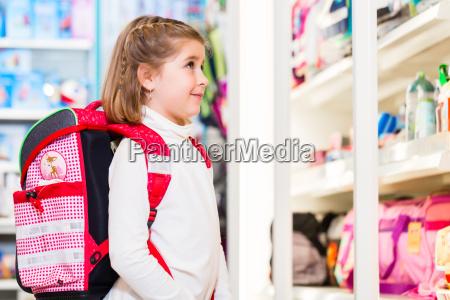 little girl choosing supplies for first