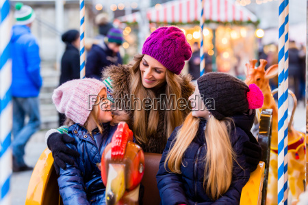family riding the carousel on christmas