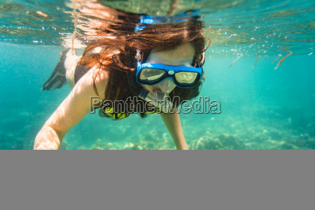 woman snorkelling over floor of tropical