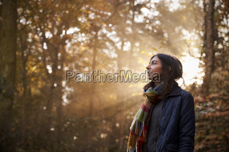 woman walks in autumn forest with