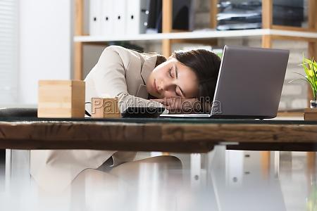 businesswoman sleeping on office desk