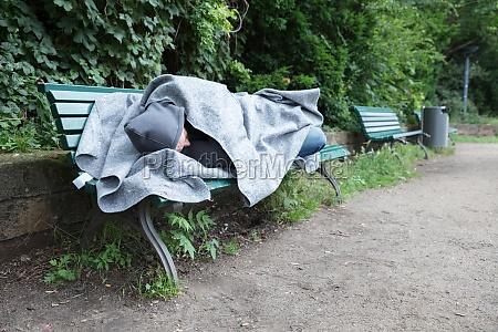 homeless man sleeping on bench