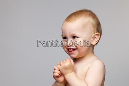 happy shirtless baby boy looking away