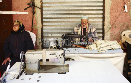 a street tailor sewing clothes in