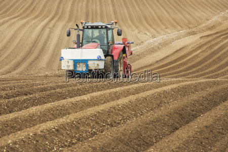 farmer ploughing and cultivating field for