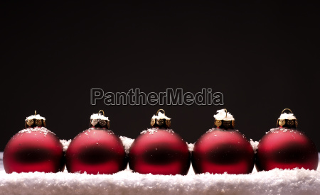 old red christmas baubles with snow