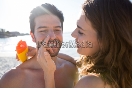 happy young woman applying sunscream on