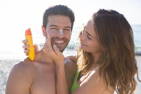 happy woman applying sunscream on smiling