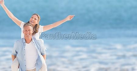 happy man piggybacking woman at beach
