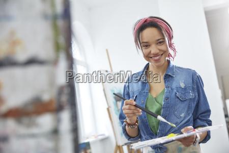 portrait smiling female artist with paintbrush